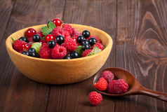 Fresh ripe berries in the bowl on the old wooden table. Useful natural food. Royalty Free Stock Images