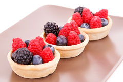 Fresh ripe berries in tartlets. On brown plate Royalty Free Stock Photos