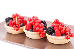 Fresh ripe berries in tartlets. On brown plate Stock Photo