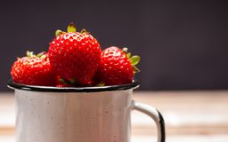 Fresh berry. Strawberries in the cup on wooden table royalty free stock photo