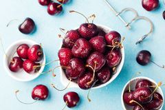 Fresh ripe black cherries in a white bowl on a blue stone background Top view Stock Images