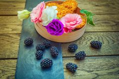 Fresh ripe blackberries, colorful eustoma flowers and biscuits Stock Photography