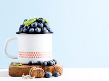 Fresh ripe blueberries in country style enamel mug on rustic wooden board over blue pastel background. Selective focus, copy space Stock Images