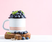 Fresh ripe blueberries in country style enamel mug on rustic wooden board over pastel pink background Stock Images