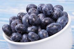 Fresh blueberries in glass bowl on blue boards, natural source of minerals, healthy dessert concept Stock Images