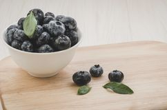 Fresh ripe blueberries with leaves in bowl on wooden tray/Fresh ripe blueberries with leaves in bowl on wooden tray. Copy space. stock photo
