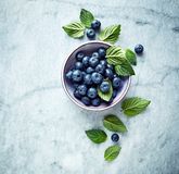 Fresh Ripe Blueberries With Mint Leaves In A Bowl On Gray Marble Background. Symbolic Image. Concept For Healthy Nutrition. Royalty Free Stock Image