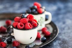 Fresh ripe blueberry and raspberry in mugs. Fresh ripe blueberry and raspberry in enamel mugs, close up Royalty Free Stock Photos
