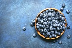 Fresh ripe blueberry in a wooden bowl.Top view with copy space. Fresh ripe blueberry in a wooden bowl over dark blue slate, stone or concrete background.Top stock image