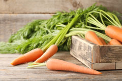 Ripe carrots. Fresh and ripe carrots in crate on wooden table Stock Image