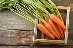 Ripe carrots. Fresh and ripe carrots in crate on wooden table Royalty Free Stock Photos