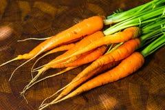 Fresh ripe carrots. On oak kitchen board Stock Images