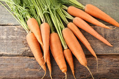 Ripe carrots. Fresh and ripe carrots on wooden table Royalty Free Stock Photos