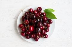 Fresh ripe cherries berries. Fresh ripe cherries. Many red cherry berries lie on white plate on white background. Vegetarian food. Top view. Flat lay stock photos