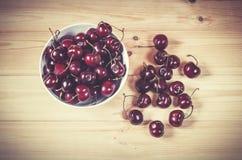 Fresh ripe cherries berries in white bowl on wooden background. Stock Photo