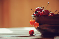 Fresh ripe cherries close up in clay handmade plate on wooden table Stock Image