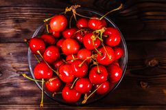 Fresh ripe cherries in glass bowl on wooden table. Top view Royalty Free Stock Photography