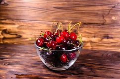 Fresh ripe cherries in glass bowl on wooden table. Fresh ripe cherries in glass bowl on rustic wooden table Royalty Free Stock Images