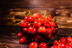 Fresh ripe cherries in glass bowl on wooden table. Fresh ripe cherries in glass bowl on rustic wooden table Royalty Free Stock Photography