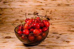 Fresh ripe cherries in glass bowl on wooden table Royalty Free Stock Photography