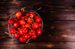 Fresh ripe cherries in glass bowl on wooden table. Top view Stock Images