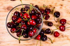 Fresh ripe cherries in glass bowl on wooden table. Top view Royalty Free Stock Photo