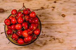 Fresh ripe cherries in glass bowl on wooden table. Top view Royalty Free Stock Images