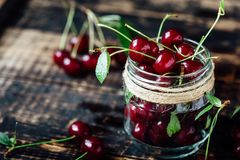 Fresh ripe cherries on a wooden table. Wooden background stock image