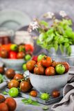 Fresh ripe cherry tomatoes in bowl on gray background stock photo