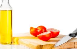 Fresh, ripe cherry tomatoes on an old chopping board. Bottle olive oil in the background Royalty Free Stock Photos