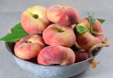 Fresh ripe chinese flat saturn peaches with leaves. Fresh ripe chinese flat saturn organic peaches with leaves Stock Photos