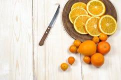 Fresh ripe citrus. Lemons, kumquat and oranges on wooden table Stock Image