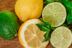 Fresh ripe citruses with mint on garden wood table Royalty Free Stock Photography