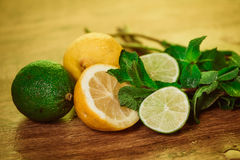 Fresh ripe citruses with mint on garden wood table Royalty Free Stock Photos