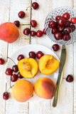 Fresh ripe colorful halved and whole peaches on white plate, scattered sweet cherries on plank wood table Stock Images