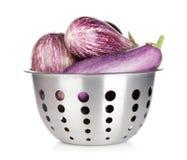 Fresh ripe eggplants in colander Stock Image