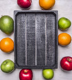 Fresh ripe fruit, apples of different varieties, oranges, mangoes laid out around a wooden box place  text  wooden rustic ba Stock Photo