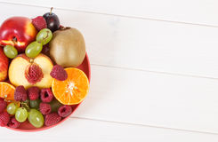 Fresh ripe fruits on plate lying on white boards, copy space for text. Fresh ripe fruits on glass plate, healthy lifestyle and nutrition, copy space for text or Stock Photography
