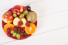 Fresh ripe fruits on plate lying on white boards, copy space for text. Fresh ripe fruits on glass plate, healthy lifestyle and nutrition, copy space for text or Stock Images