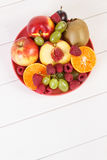 Fresh ripe fruits on plate lying on white boards, copy space for text. Fresh ripe fruits on glass plate, healthy lifestyle and nutrition, copy space for text or Royalty Free Stock Photos