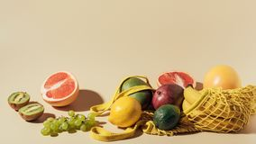 Fresh ripe fruits and string bag on brown royalty free stock photos
