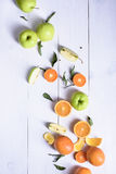 Fresh ripe fruits on a white table. Oranges and green apples sli Stock Image