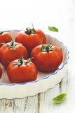 Fresh ripe grape tomatoes. Inside a white ceramic oven dish on wooden table, rustic style Stock Photo
