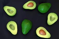 Fresh ripe green avocado fruits, whole and cut in half, on black. Fresh looking, ripe green avocado fruits, whole and cut in half, in random arrangement, rotated stock image