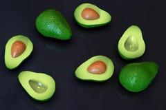 Fresh ripe green avocado fruits, whole and cut in half, on black. Fresh looking, ripe green avocado fruits, whole and cut in half, in random arrangement, rotated stock photos