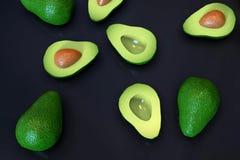Fresh ripe green avocado fruits, whole and cut in half, on black. Fresh looking, ripe green avocado fruits, whole and cut in half, in random arrangement, rotated royalty free stock photo