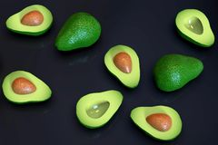 Fresh ripe green avocado fruits, whole and cut in half, on black. Fresh looking, ripe green avocado fruits, whole and cut in half, in random arrangement, rotated stock images