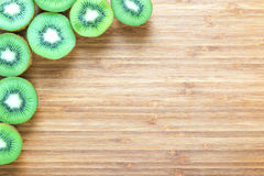Fresh ripe green kiwi fruits sliced in half on a wooden cutting board. Nature fruit concept. Background for healthy diet themes. Stock Photo