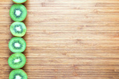 Fresh ripe green kiwi fruits sliced in half on a wooden cutting board. Nature fruit concept. Background for healthy diet themes. Royalty Free Stock Image