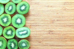 Fresh ripe green kiwi fruits sliced in half on a wooden cutting board. Nature fruit concept. Background for healthy diet themes. Royalty Free Stock Photography